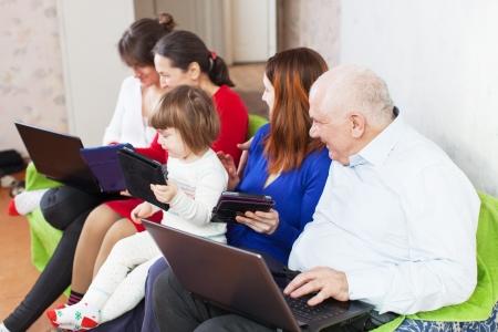 few: happy  family using few laptops in home