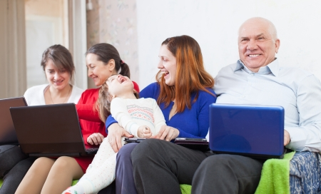 Happy family uses few electronic devices photo