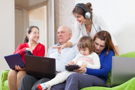 Famaly or group of people  uses few various electronic devices  photo