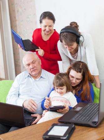musica electronica: Familia multigeneracional feliz utiliza unos varios dispositivos electr�nicos