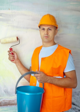 unskilled worker: male house painters with paint roller in new house
