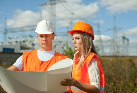 electrical contractor:  two workers wearing protective helmet works at electrical power station. Stock Photo