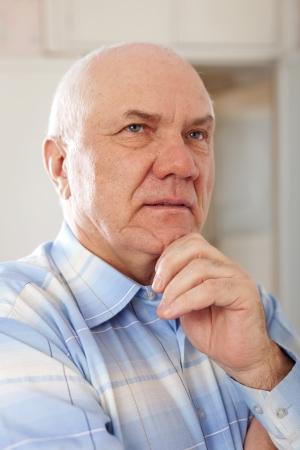 wistful: portrait of wistful senior man in interior