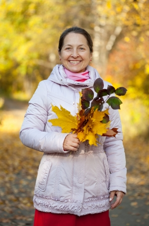 Portrait of happy mature woman  in autumn park photo
