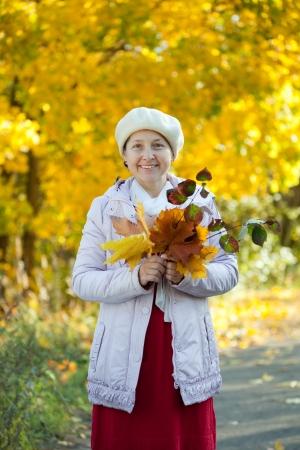 Portrait of happy mature woman  in autumn park Stock Photo - 19628980