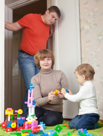 woman only: Happy mother and baby plays with toys in home. Focus on woman only