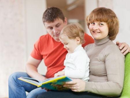 Happy parents with child looks the book in home interior photo