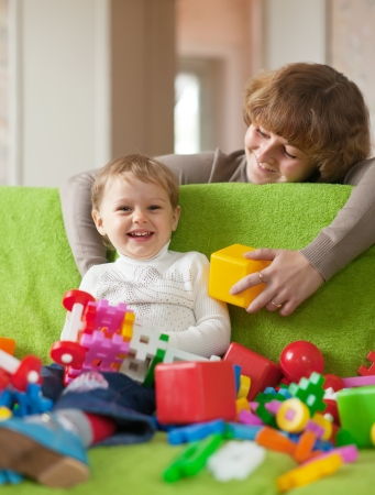 adult toys: Happy mother plays with child in home interior