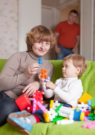 Happy mother and child plays with toys in home photo