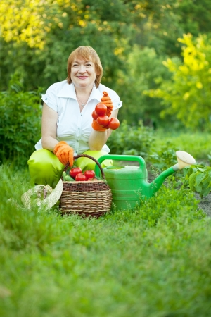Happy mature woman in vegetables garden photo