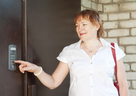 Mature woman using house intercom outdoor photo