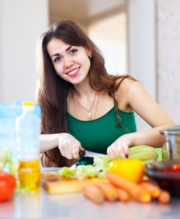 Happy beautiful woman cutting vegetables at her kitchen at home photo