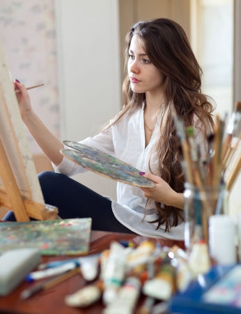 artist paints picture on canvas with oil paints in her workshop photo