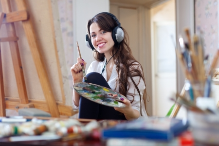 picture person: Long-haired woman in headphones  paints with oil colors on canvas in workshop