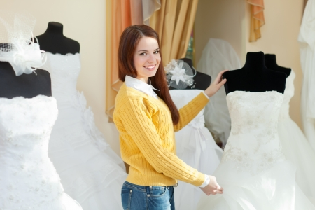 Smiling pretty bride chooses wedding dress in bridal boutique photo