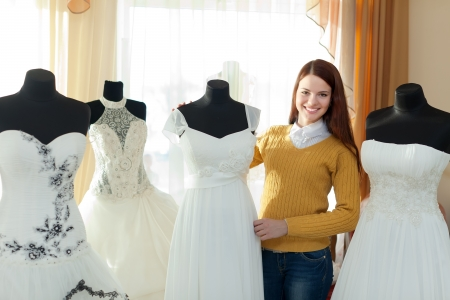 Smiling woman chooses  wedding dress in bridal boutique photo