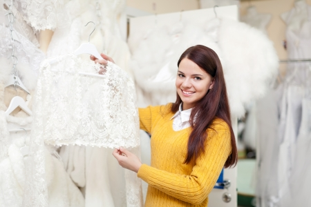 Smiling woman chooses wedding outfit at bridal store photo