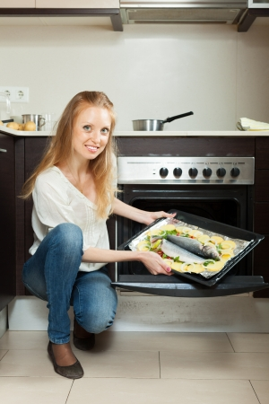 woman cooking fish in oven at home kitchen photo