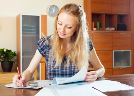 parsimony: serious long-haired woman fills in the questionnaire at home Stock Photo