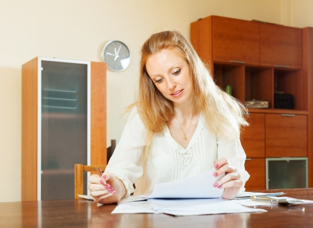 parsimony: serious blonde woman looking financial documents at table in home Stock Photo