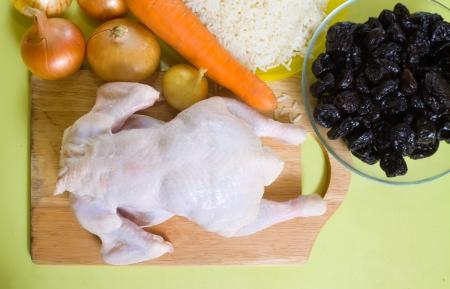 pruneau: Poulet cru avec des pruneaux et du riz sur la table de cuisson