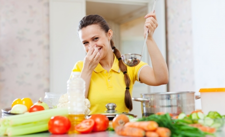frowy:  young woman holding her nose because of bad smell from food at kitchen