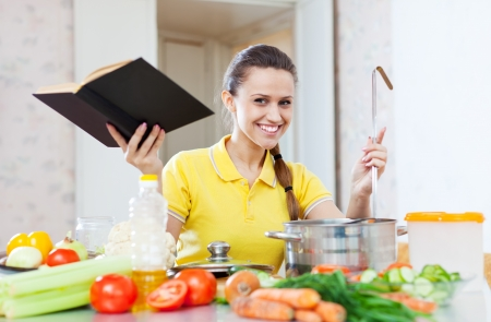 happy woman cooking  vegetables with book at domestic kitchen    photo
