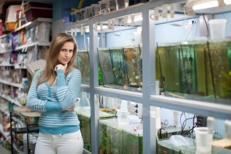 Woman near aquariums with fishes in pet-shop photo