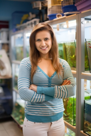 Woman near aquariums with fishes in pet-shop Stock Photo - 19761247