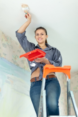 Woman paints ceiling with brush at home Stock Photo - 19761236