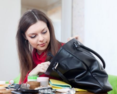reticule: Girl can not finding anything in her purse at table in home Stock Photo