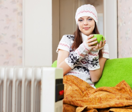 Beautiful woman relaxing near oil heater at home with cup in winter