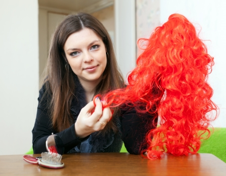 peruke: Young brunette woman with red false hair at home Stock Photo