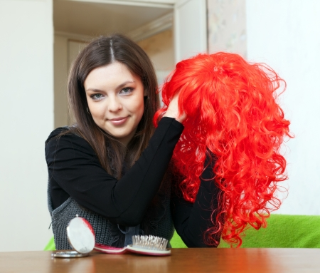 periwig:  brunette woman with red periwig at home Stock Photo