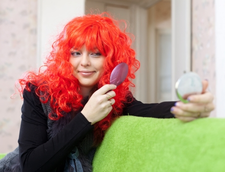 peruke: Woman in red periwig looks to mirror at home Stock Photo