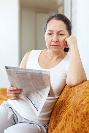 wistful:  serious and wistful mature woman looks newspaper at home