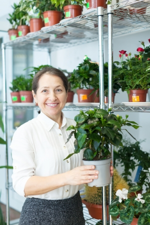 Happy mature woman with hibiscus in flower store photo