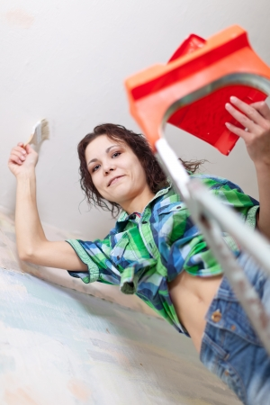 modifying: Happy girl paints ceiling with brush at home