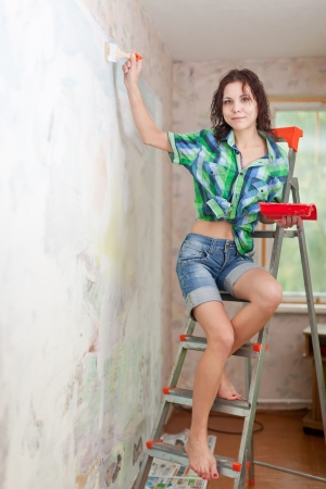 girl paints wall with brush at home photo