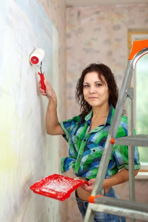 modifying: woman paints wall with roller at home Stock Photo