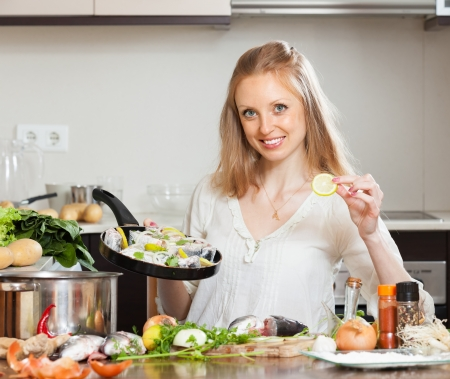 cook griddle: Smiling girl cooking fish with lemon in frying pan at  kitchen