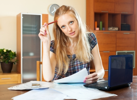 parsimony: Blonde woman with financial document and laptop at home