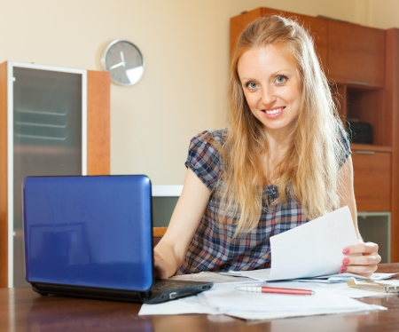 utility payments: smiling long-haired woman working with financial documents  at home interior