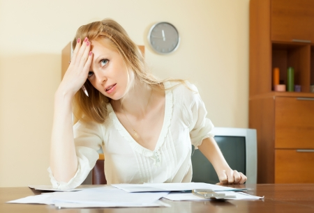 pensive woman reading financial documents at home photo
