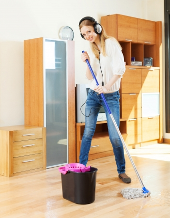 girl in headphones washing floor with mop in living room photo