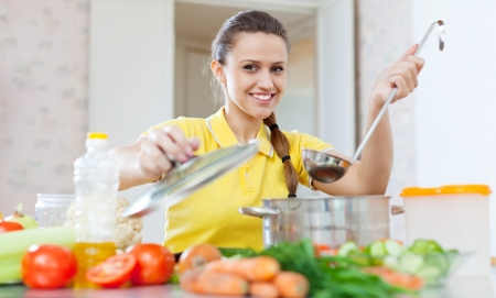 Portrait of  woman cooking  vegetarian food in saucepan at home kitchen    photo