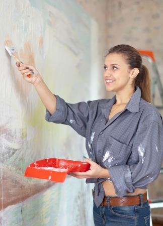 modifying: Happy woman paints wall with brush Stock Photo