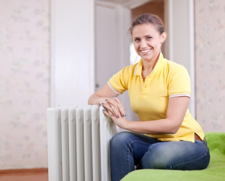 heat register:  Happy woman near oil heater in home