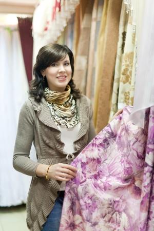 woman chooses the draperies at market photo