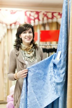 woman chooses draperies at market photo